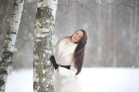 Pretty woman in a winter park standing next to a birch Stock Photo - 8296794
