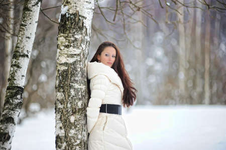Pretty woman in a winter park standing next to a birch Stock Photo - 8296798