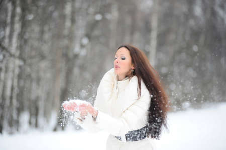 fur hood: Beautiful woman in winter park, blowing snow playfully