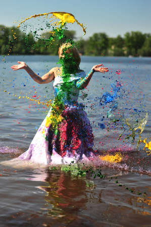 The girl in a wedding dress standing in water poured by a paint photo