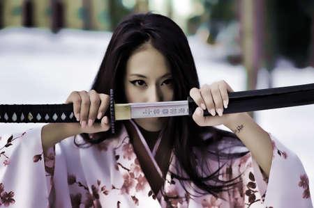 Young japanese woman with samurai sword fashion photo