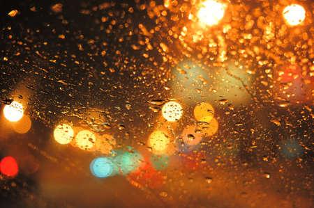 Gotas de lluvia sobre portarretrato de vidrio de la ventana. borrosa de fondo de la noche con luces de colores Foto de archivo - 8412613