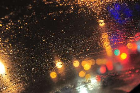 gotas de agua: Gotas de lluvia sobre portarretrato de vidrio de la ventana. borrosa de fondo de la noche con luces de colores Foto de archivo