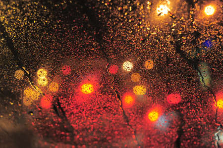 Raindrops over window glass closeup. blurred night background with coloured lights Stock Photo