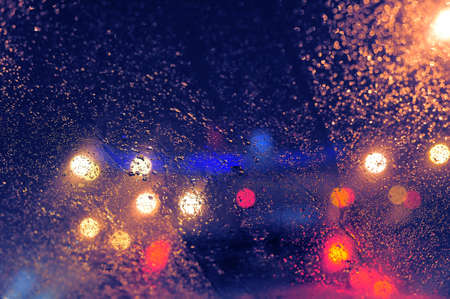 Raindrops over window glass closeup. blurred night background with coloured lights Stock Photo - 8412629