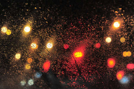 Raindrops over window glass closeup. blurred night background with coloured lights Stock Photo - 8412627