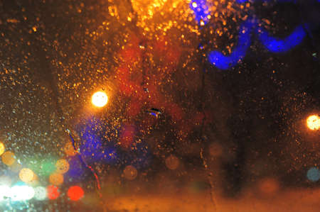 Raindrops over window glass closeup. blurred night background with coloured lights photo