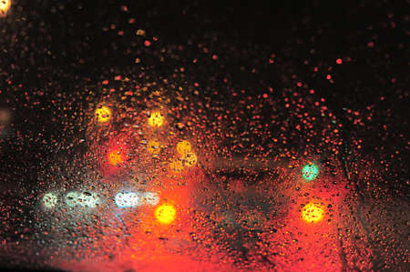 Raindrops over window glass closeup. blurred night background with coloured lights Stock Photo - 8412600
