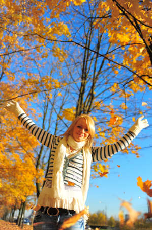 Portrait of a happy woman playing with autumn leaves  photo