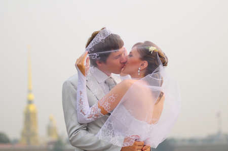 A couple about to kiss under a veil outdoors photo