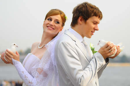 Two pigeons and newly-married couple photo