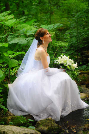 a bride sitting by the stream photo