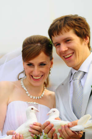 Two pigeons and newly-married couple Stock Photo - 8455957