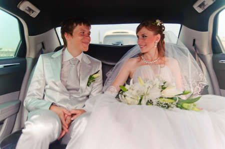 Smiling newlyweds inside the limo photo
