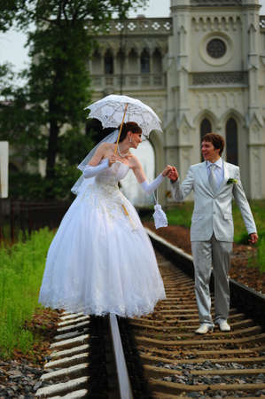 Newly-married couple walking on rails photo