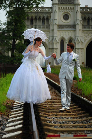 newly wedded couple: Newly-married couple walking on rails Stock Photo