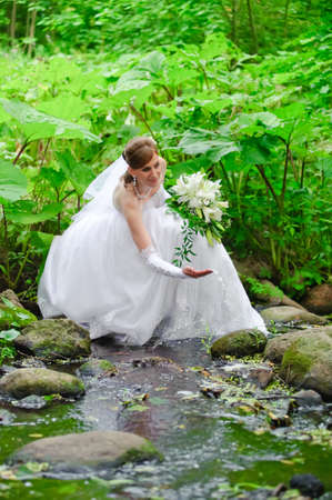 Bride poses in a Creek in her wedding dress.