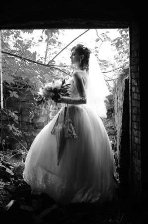 Bride on the ruins of a brick house photo