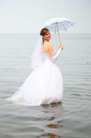 Bride standing in water photo