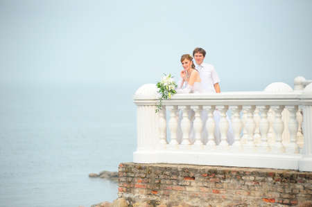 the bride and groom on the terrace by the sea photo