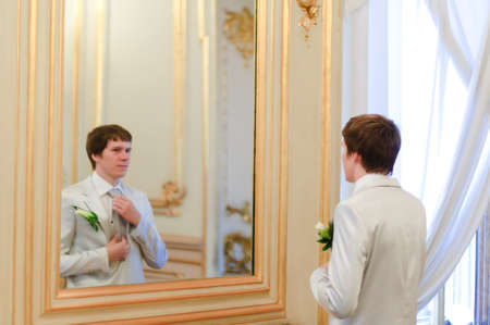 long life: groom convalescent tie before the mirror