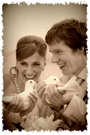 newlyweds with pigeons in hands photo