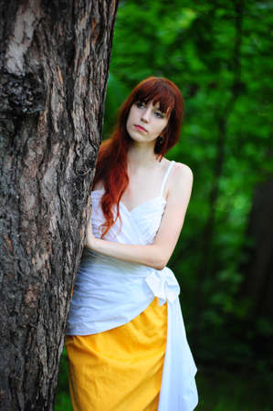 The girl in an elegant dress  about a tree Stock Photo - 10325931