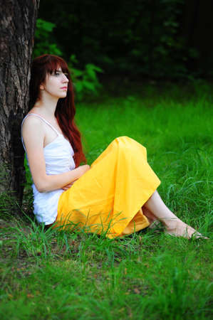 thinking girl sitting near tree photo