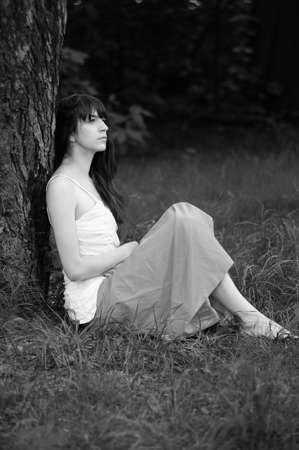 thinking girl sitting near tree photo