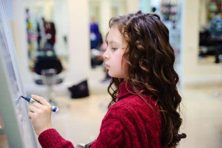 ni�os pensando: la chica escribiendo en un tablero Foto de archivo