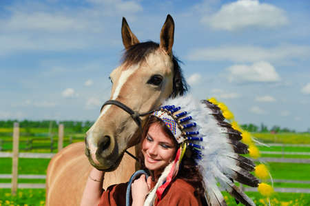 The girl in a suit of the American Indian near to a horse photo