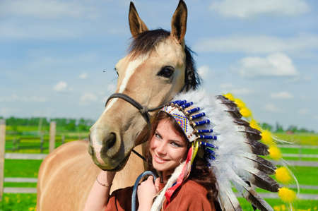 regalia: Girl standing near a horse, wearing a Native American headdress. Stock Photo