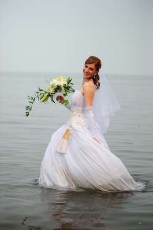 a bride in a dress in the water photo