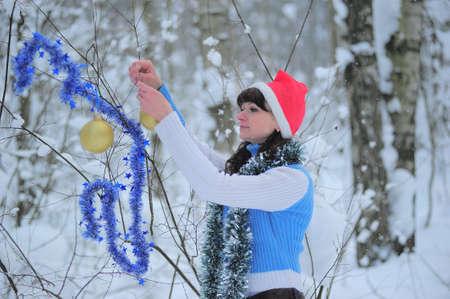 Girl decorating the tree in Santa's cap Stock Photo - 9381451