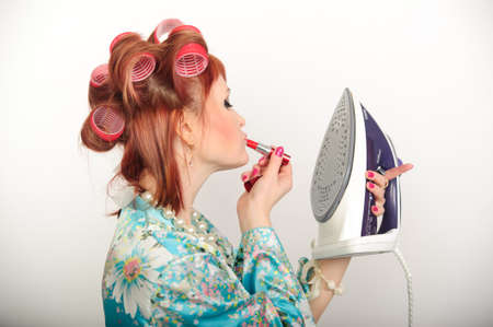 Portrait of redhead woman looking at her reflection in iron and checking in her make-up photo