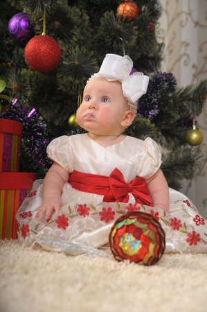 Baby girl sitting next to the christmas tree Stock Photo - 8653874