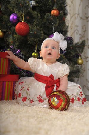 Baby girl sitting next to the christmas tree photo