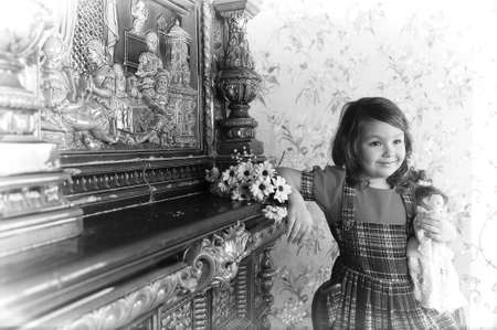 little girl with a doll in hands. photos in retro style photo