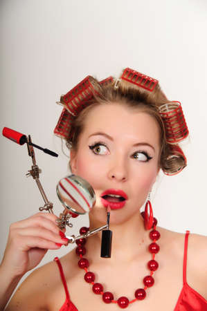 A housewife with hair-curlers and with a magniglass Stock Photo - 8645834