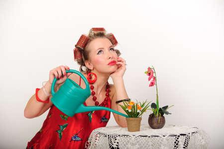 Dreamy woman watering the flowers