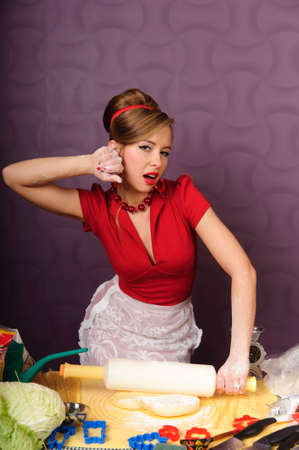 A woman prepares some dough for baking food. photo