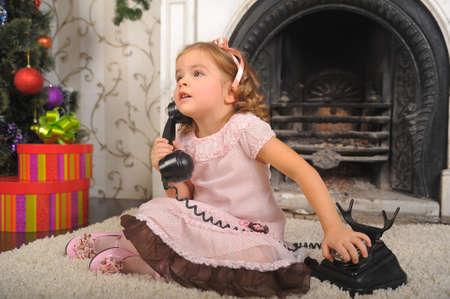 Little girl in  dress talking vintage phone. Stock Photo - 8653853