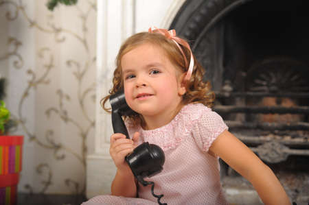 Little girl in  dress talking vintage phone. photo