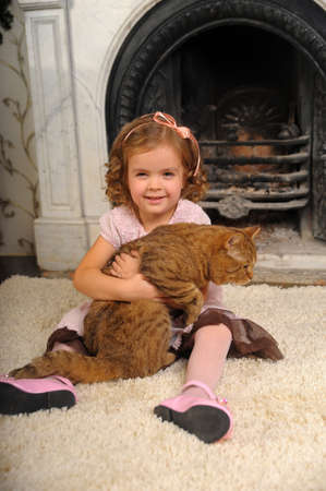 little girl with a cat in her arms photo