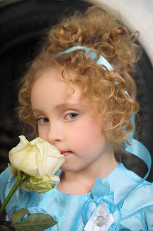 Beautiful little girl with blond curly hair holding a white rose. photo