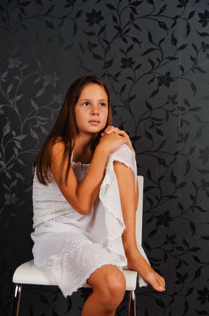 The girl in white clothes sitting on a chair in studio photo