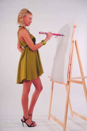 Beauty teenager girl painting on blank white canvas photo