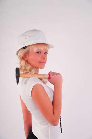 Young blond businesswoman, hammer helmet photo