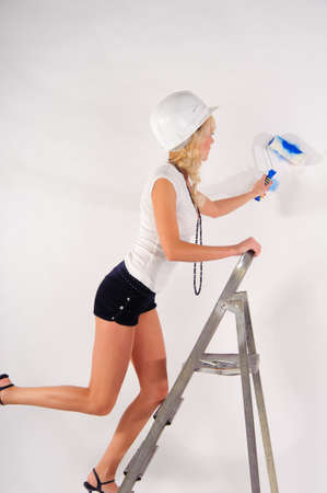 young woman painting the walls photo