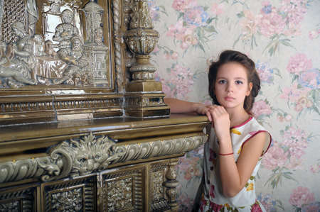 girl with retro hairdo about antique stove photo